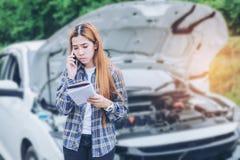 Jovem mulher que chama para o auxílio com seu carro dividido por t foto de stock