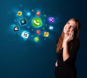 Jovem mulher que chama pelo telefone com vários ícones Foto de Stock Royalty Free