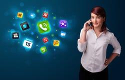Jovem mulher que chama pelo telefone com vários ícones Fotos de Stock Royalty Free