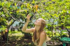 Jovem mulher que cheira o fruto de paixão no jardim fotos de stock