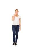 Jovem mulher que cobre sua boca com a mão Fotografia de Stock