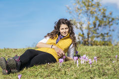 Jovem mulher que coloca em um prado com açafrões roxos Foto de Stock Royalty Free