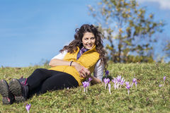 Jovem mulher que coloca em um prado com açafrões roxos Fotos de Stock Royalty Free