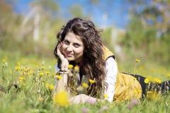 Jovem mulher que coloca em um prado com flores amarelas Imagem de Stock Royalty Free