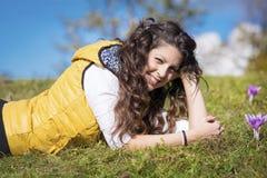 Jovem mulher que coloca em um prado completamente de açafrões roxos Foto de Stock