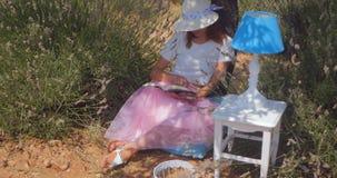 Jovem mulher que coloca lendo um livro sob a árvore video estoque