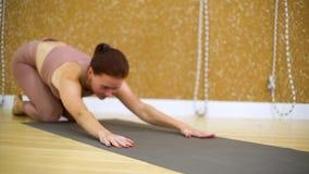 Jovem mulher que coloca na esteira, fazendo exercícios da ioga no estúdio da ioga vídeos de arquivo