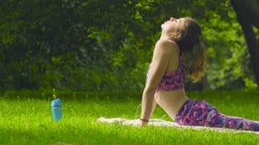 Jovem mulher que coloca na grama no parque filme