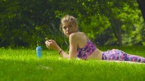 Jovem mulher que coloca na grama no parque vídeos de arquivo