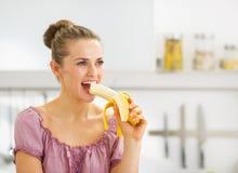 Jovem mulher que come a banana na cozinha Fotografia de Stock Royalty Free