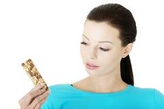 Jovem mulher que come a barra de chocolate do cereal Fotos de Stock