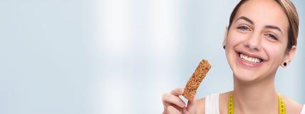 Jovem mulher que come a barra do muesli Foto de Stock