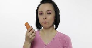 A jovem mulher que come a cenoura e diz yum A menina toma a primeira mordida e di-la quer morder filme