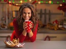 Jovem mulher que come cookies do Natal na cozinha fotografia de stock royalty free
