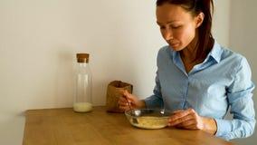 A jovem mulher que come flocos de milho com leite para o caf? da manh? na cozinha na manh? video estoque