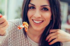 Jovem mulher que come o alimento chinês em um restaurante, tendo seu lunc fotografia de stock