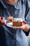Jovem mulher que come o bolo de cenoura Foto de Stock