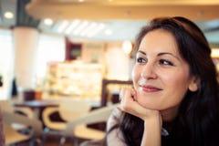 Jovem mulher que come o café em um café foto de stock royalty free