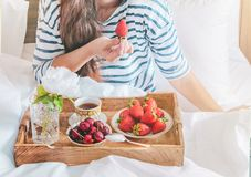 Jovem mulher que come o caf? da manh? saud?vel na cama Café da manhã romântico com morangos e a cereja doce em uma cama fotos de stock