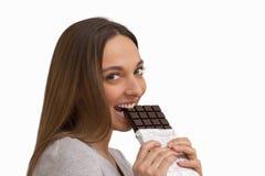Jovem mulher que come o chocolate no fundo branco Fotos de Stock Royalty Free