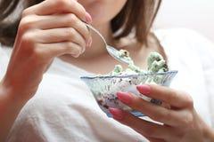 Jovem mulher que come o gelado com colher Foto de Stock