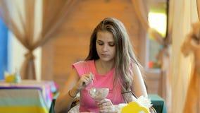 Jovem mulher que come o gelado em um café vídeos de arquivo