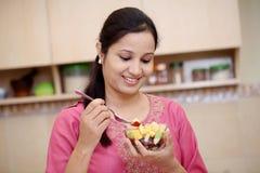 Jovem mulher que come a salada de fruto foto de stock