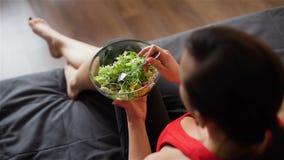 Jovem mulher que come a salada do vegetariano em um sofá vídeos de arquivo