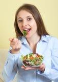 Jovem mulher que come a salada na sala de visitas fotos de stock