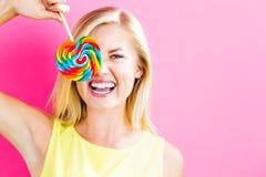 Jovem mulher que come um pirulito Imagem de Stock Royalty Free
