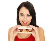 Jovem mulher que come um sanduíche do bacon Imagens de Stock Royalty Free