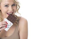 Jovem mulher que come uma barra de chocolate Imagem de Stock