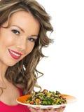 Jovem mulher que come uma salada asiática do estilo do arco-íris aromático Foto de Stock