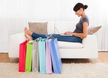 Jovem mulher que compra em linha foto de stock