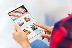 Jovem mulher que compra em linha no tablet pc foto de stock