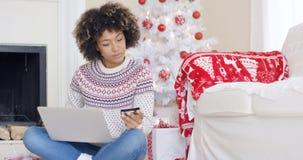 Jovem mulher que compra presentes do Natal em linha foto de stock