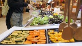 Jovem mulher que compra vegetais orgânicos para a salada O vegetariano leva embora o conceito saudável do estilo de vida da dieta video estoque