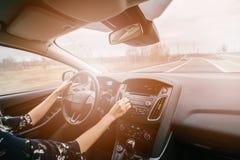 Jovem mulher que conduz um carro e que ajusta o áudio do carro fotografia de stock