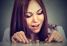 Jovem mulher que conta o dinheiro que empilha acima das moedas fotografia de stock royalty free