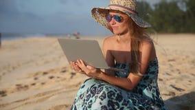 Jovem mulher que conversa no computador na praia filme