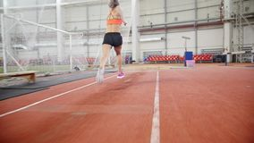 Jovem mulher que corre e que executa um salto longo na arena esportiva filme