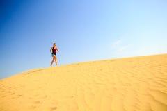 Jovem mulher que corre em dunas do deserto da areia Fotos de Stock