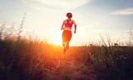 Jovem mulher que corre em uma estrada rural no por do sol Imagens de Stock