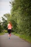 Jovem mulher que corre fora em um dia de inverno ensolarado bonito fotografia de stock royalty free