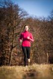 Jovem mulher que corre fora em um inverno/dia ensolarados bonitos da queda fotografia de stock