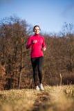 Jovem mulher que corre fora em um inverno/dia ensolarados bonitos da queda foto de stock royalty free