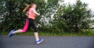 Jovem mulher que corre fora em um inverno/dia ensolarados bonitos da queda imagem de stock