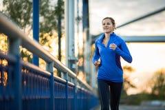 Jovem mulher que corre fora, em uma cidade foto de stock royalty free