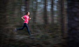 Jovem mulher que corre fora em uma floresta, indo rapidamente foto de stock royalty free