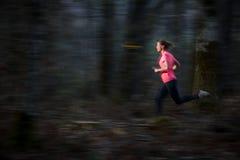 Jovem mulher que corre fora em uma floresta, indo rapidamente fotos de stock royalty free